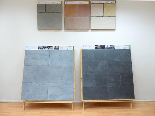 Deux grandes planches à dessin avec de l'ardoise appuyée contre un mur, trois plus petits motifs au-dessus d'eux
